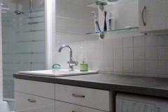 Fehér mosdószekrény süllyesztett mosdókagylóval, felül nyitott polcokkal és zárt szekrénnyel