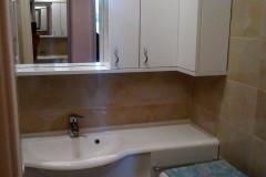 Magasfényű fehér mosdószekrény, L alakú felső szekrénnyel kicsi fürdőszobába